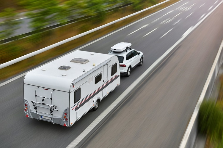 Car pulling camper trailer on road
